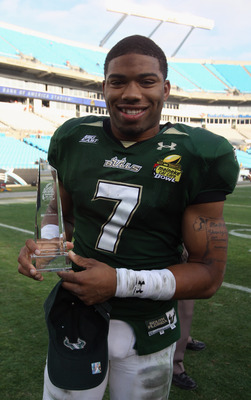 CHARLOTTE, NC - DECEMBER 31:  B.J. Daniels #7 of the USF Bulls stands with the MVP trophy after a 31-26 victory over the Clemson Tigers at Bank of America Stadium on December 31, 2010 in Charlotte, North Carolina.  (Photo by Streeter Lecka/Getty Images)
