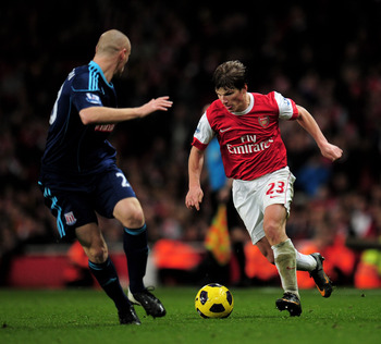 LONDON, ENGLAND - FEBRUARY 23:  Andy Wilkinson (L) of Stoke tracks Andrey Arshavin of Arsenal as he runs with the ball during the Barclays Premier League match between Arsenal and Stoke City at the Emirates Stadium on February 23, 2011 in London, England.