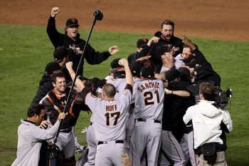 ARLINGTON, TX - NOVEMBER 01:  Catcher Buster Posey #28, Aubrey Huff #17, Freddy Sanchez #21 and Matt Cain #18 (top L) of the San Francisco Giants celebrate on the field with their teammates after the Giants won 3-1 against the Texas Rangers in Game Five o