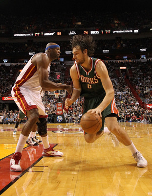 MIAMI, FL - JANUARY 04:  Andrew Bogut #6 of the Milwaukee Bucks dribbles past Erick Dampier #25 of the Miami Heat during a game at American Airlines Arena on January 4, 2011 in Miami, Florida. NOTE TO USER: User expressly acknowledges and agrees that, by