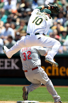 OAKLAND, CA - JUNE 23:  Daric Barton #10 of the Oakland Athletics leaps for a overthrown ball as Jay Bruce #32 of of the Cincinnati Reds looks on during an MLB game at the Oakland-Alameda County Coliseum on June 23, 2010 in Oakland, California. (Photo by