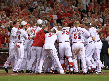 CINCINNATI - SEPTEMBER 11:  Joey Votto #19 of the Cincinnati Reds is mobbed by his teammates after hitting a game winning home run during the game against the Pittsburg Pirates at Great American Ball Park on September 11, 2010 in Cincinnati, Ohio. The Red