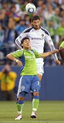 SEATTLE, WA - OCTOBER 31:  Omar Gonzalez #4 of the Los Angeles Galaxy heads the ball against Fredy Montero #17 of the Seattle Sounders FC during the 1st leg playoff game at Qwest Field on October 31, 2010 in Seattle, Washington. (Photo by Otto Greule Jr/G