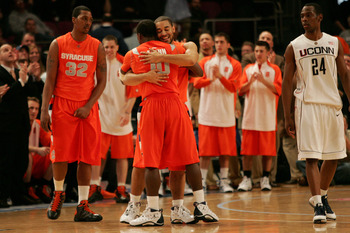 NEW YORK - MARCH 12:  Justin Thomas #2 and Jonny Flynn #10 of the Syracuse Orange celebrate late in the sixth overtime as Craig Austrie #24 of the Connecticut Huskies looks on during the quarterfinal round of the Big East Tournament at Madison Square Gard