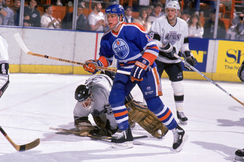 INGLEWOOD, CA - 1988:  Jimmy Carson #12 of the Edmonton Oilers skates past Los Angeles Kings goalkeeper Rob Stauber #35 who fall out of position in front of the crease during a game in 1988 at the Great Western Forum in Inglewood, California.  (Photo by M