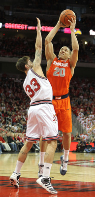 LOUISVILLE, KY - FEBRUARY 12:  Brandon Triche #20 of the Syracuse Orange shoots the ball while defended by Mike Marra #33 of the Louisville Cardinals during the Big East Conference game at the KFC Yum! Center on February 12, 2011 in Louisville, Kentucky.