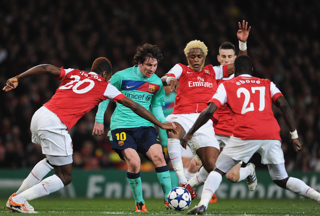 LONDON, ENGLAND - FEBRUARY 16:  Lionel Messi of Barcelona is challenged by Alex Song of Arsenal during the UEFA Champions League round of 16 first leg match between Arsenal and Barcelona at the Emirates Stadium on February 16, 2011 in London, England.  (P