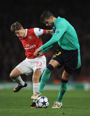 LONDON, ENGLAND - FEBRUARY 16: Andrey Arshavin of Arsenal challenges Gerard Pique of Barcelona during the UEFA Champions League round of 16 first leg match between Arsenal and Barcelona at the Emirates Stadium on February 16, 2011 in London, England.  (Ph