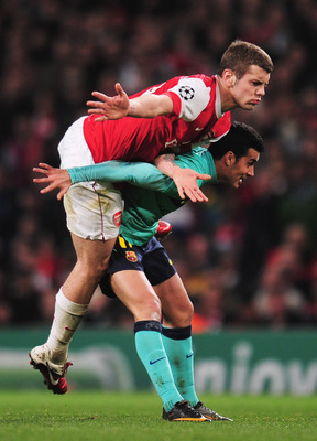 LONDON, ENGLAND - FEBRUARY 16: Jack Wilshere of Arsenal is held up by Pedro Rodriguez of Barcelona during the UEFA Champions League round of 16 first leg match between Arsenal and Barcelona at the Emirates Stadium on February 16, 2011 in London, England.