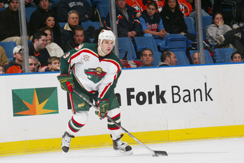 UNIONDALE, NY - DECEMBER 13:  Right wing Alexandre Daigle #9 of the Minnesota Wild handles the puck against the New York Islanders at the Nassau Coliseum on December 13, 2005 in Uniondale, New York. The Wild defeated the Islanders 4-3. (Photo by Bruce Ben