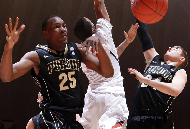 CHAMPAIGN, IL - FEBRUARY 13: JaJuan Johnson #25 and Ryne Smith #24 of the Purdue Boilermakers defend a shot by Jereme Richmond #22 of the Illinois Fighting Illini at Assembly Hall on February 13, 2011 in Champaign, Illinois. Purdue defeated Illinois 81-70