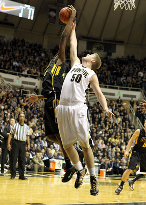 WEST LAFAYETTE, IN - JANUARY 09:  Travis Carroll #50 of the Purdue Boilermakers reaches for a rebound against Devon Archie #35 of the Iowa Hawkeyes during the Big Ten Conference game at Mackey Arena on January 9, 2011 in West Lafayette, Indiana. Purdue wo