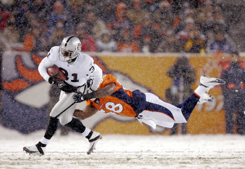 DENVER - NOVEMBER 28:  Linebacker Terry Pierce #58 of the Denver Broncos dives in an attempt to tackle punt returner Phillip Buchanon #31 of the Oakland Raiders on November 28, 2004 at Invesco Field at Mile High Stadium in Denver, Colorado. The Raiders wo
