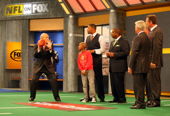 LOS ANGELES, CA - DECEMBER 12:  (L-R) FOX NFL Sunday host Terry Bradshaw demonstrates a move to St. Jude Children's Research Hospital patient Markell, analyst Michael Strahan, host Curt Menefee, analysts Jimmy Johnson and Howie Long and former NFL referee