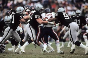 LOS ANGELES, CA - DECEMBER 27:  Bob Buczkowski #95 and Greg Townsend #93 of the Los Angeles Raiders tackle running back Walter Payton #34 of the Chicago Bears during the game at the Los Angeles Memorial Coliseum on December 27, 1987 in Los Angeles, Califo