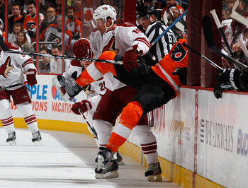 PHILADELPHIA - FEBRUARY 22:  Shane Doan #19 of the Phoenix Coyotes knocks Chris Pronger #20 of the Philadelphia Flyers into the boards on February 22, 2011 at the Wells Fargo Center in Philadelphia, Pennsylvania. Tonight marks Doan's 1,098th game with the
