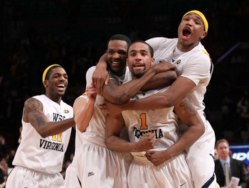 NEW YORK - MARCH 11: Da'Sean Butler #1 of the West Virginia Mountaineers celebrates with teammates John Flowers #41, Devin Ebanks #3 and Kevin Jones #5 after making a game winning three pointer to defeat the Cincinnati Bearcats during the quarterfinal of