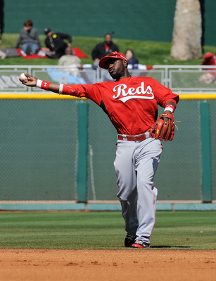 GOODYEAR, AZ - FEBRUARY 27:  Brandon Phillips #4 of the Cincinnati Reds throws the ball to first base during warm ups in between innings against the Cleveland Indians at Goodyear Ballpark on February 27, 2011 in Goodyear, Arizona.  (Photo by Norm Hall/Get