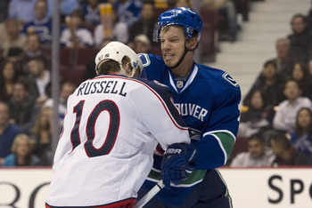 VANCOUVER, CANADA - MARCH 1: Mikael Samuelsson #26 of the Vancouver Canucks punched Kris Russell #10 of the Columbus Blue Jackets while battling in front of the net during the second period in NHL action on March 01, 2011 at Rogers Arena in Vancouver, Bri
