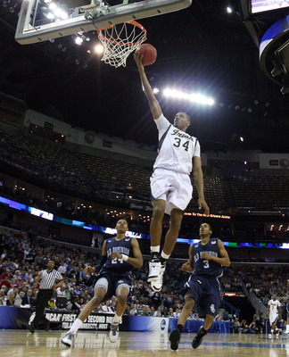 NEW ORLEANS - MARCH 18:  Carleton Scott #34 of the Notre Dame Fighting Irish scores despite the defense of the Old Dominion Monarchs Darius James (3) and Kent Bazemore (24) during the first round of the 2010 NCAA mens basketball tournament at the New Orle
