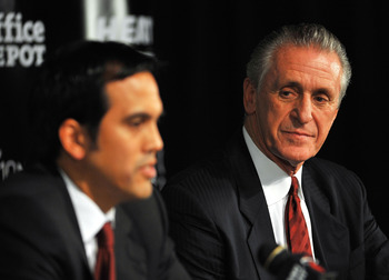 MIAMI - JULY 09:  Head coach Erik Spoelstra (L) and President Pat Riley (R)  of the Miami Heat talk during a press conference after a welcome party for new teammates LeBron James, Dwyane Wade, and Chris Bosh at American Airlines Arena on July 9, 2010 in M