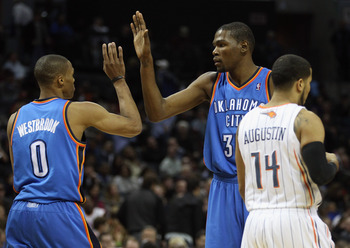 CHARLOTTE, NC - DECEMBER 21:  Teammates Kevin Durant #35 and Russell Westbrook #0 of the Oklahoma Thunder celebrate after a basket as D.J. Augustin #14 of the Charlotte Bobcats walks away during their game at Time Warner Cable Arena on December 21, 2010 i