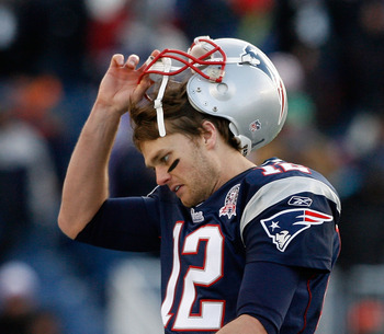 FOXBORO, MA - JANUARY 10:  Tom Brady #12 of the New England Patriots takes off his helmet as he walks to the sideline against the Baltimore Ravens during the 2010 AFC wild-card playoff game at Gillette Stadium on January 10, 2010 in Foxboro, Massachusetts