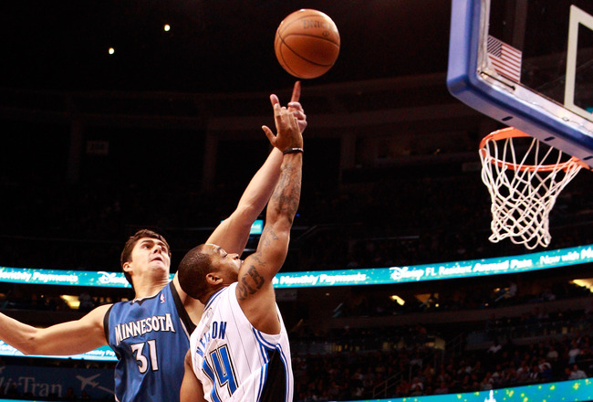 ORLANDO, FL - NOVEMBER 03:  Jameer Nelson #14 of the Orlando Magic attempts to score over Darko Milicic #31 of the Minnesota Timberwolvesduring the game at Amway Arena on November 3, 2010 in Orlando, Florida.  NOTE TO USER: User expressly acknowledges and