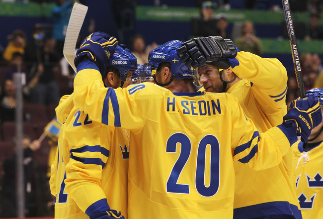 VANCOUVER, BC - FEBRUARY 19:  Henrik Sedin #20 of Sweden and teammates celebrate the goal scored by Daniel Alfredsson #11 against Belarus during the ice hockey men's preliminary game on day 8 of the Vancouver 2010 Winter Olympics at Canada Hockey Place on