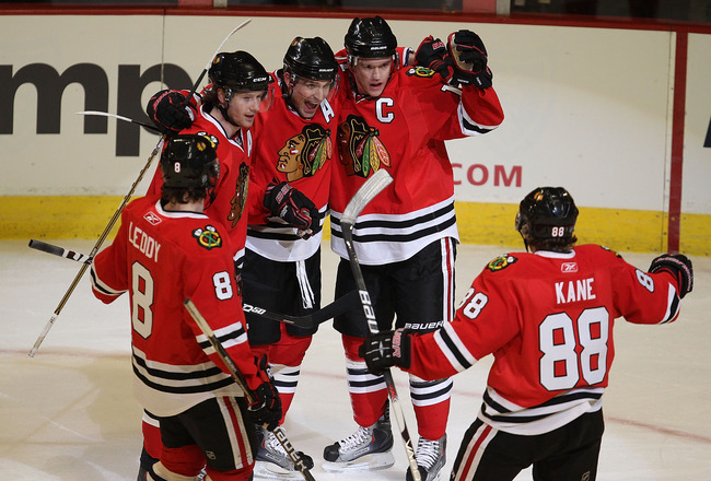 CHICAGO, IL - MARCH 02: (L-R) Nick Leddy #8, Duncan Keith #2, Patrick Sharp #10 and Jonathan Toews #19 of the Chicago Blackhawks welcome teammate Patrick Kane #88 to celebrate Toew's goal against the Calgary Flames at the United Center on March 2, 2011 in