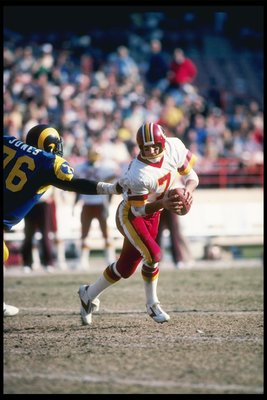20 Dec 1981:  Washington Redskins quarterback Joe Theismann avoids Los Angeles Rams defensive lineman Cody Jones during game at Anaheim Stadium in Anaheim, California.  The Redskins won the game 30-7. Mandatory Credit: Allsport  /Allsport