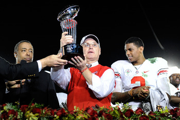 PASADENA, CA - JANUARY 01:  (C) Head coach Jim Tressel of the Ohio State Buckeyes celebrates with the Rose Bowl championship trophy as quarterback Terrelle Pryor #2 looks on after the buckeyes 26-17 win in the 96th Rose Bowl game over the Oregon Ducks on