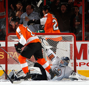 PHILADELPHIA, PA - MARCH 08:  Jeff Carter #17 of the Philadelphia Flyers skates away from downed goaltender Devan Dubnyk #40 of the Edmonton Oilers after Carter just scored a goal during the first period of an NHL hockey game while Chris Pronger #20 of th