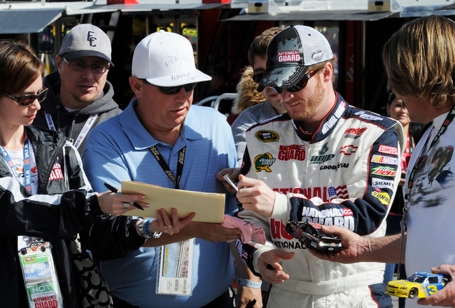 LAS VEGAS, NV - MARCH 05:  Dale Earnhardt Jr., driver of the #88 National Guard/Amp Energy Chevrolet, signs his autograph in the garage area during practice for the NASCAR Sprint Cup Series Kobalt Tools 400 at Las Vegas Motor Speedway on March 5, 2011 in