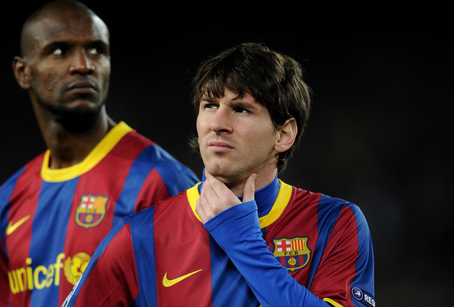 BARCELONA, SPAIN - MARCH 08:  Lionel Messi (R) of Barcelona stands besides his teammate Eric Abidal prior to the start of the UEFA Champions League round of 16 second leg match between Barcelona and Arsenal on March 8, 2011 in Barcelona, Spain.  (Photo by