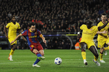 BARCELONA, SPAIN - MARCH 08: Xavi Hernandez of FC Barcelona (2ndL) scores his team's second goal under a challenge by Bacary Sagna of Arsenal during the UEFA Champions League round of 16 second leg match between Barcelona and Arsenal at the Camp Nou stadi