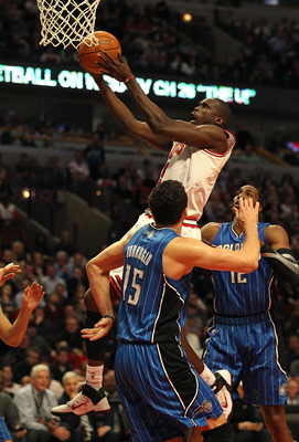 CHICAGO, IL - JANUARY 28: Loul Deng #9 of the Chicago Bulls puts up a shot against Hedo Turkoglu #15 and Dwight Howard #12 of the Orlando Magic at the United Center on January 28, 2011 in Chicago, Illinois. The Bulls defeated the Magic 99-90. NOTE TO USER