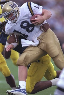 28 Sep 1996:  Quarterback Cade McNown of the UCLA Bruins is tackled by David Bowens of the Michigan Wolverines during the Bruins 38-9 loss to the Michigan Wolverines at Michigan Stadium in Ann Arbor, Michigan.  Mandatory Credit: Brian Bahr  /Allsport