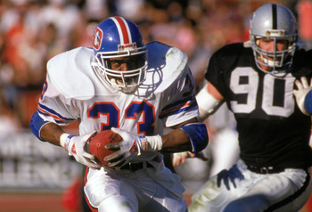 LOS ANGELES - DECEMBER 4:  Running back Tony Dorsett #33 of the Denver Broncos runs away from defensive end Mike Wise #90 of the Los Angeles Raiders during a game at the Los Angeles Memorial Coliseum on December 4, 1988 in Los Angeles, California.  The Ra