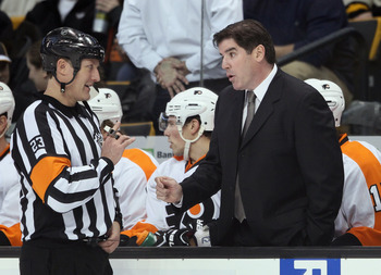 BOSTON, MA - JANUARY 13:  Head coach Peter Laviolette of the Philadelphia Flyers talks with referee Brad Watson before the start of the second period against the Boston Bruins on January 11, 2011 at the TD Garden in Boston, Massachusetts.  (Photo by Elsa/