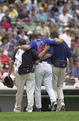CHICAGO - JUNE 26:  Pitcher Jason Bere #46 of the Chicago Cubs is helped off the field by the training staff after getting injured against the Cincinnati Reds during the game on June 26, 2002 at Wrigley Field in Chicago, Illinois. The Reds defeated the Cu