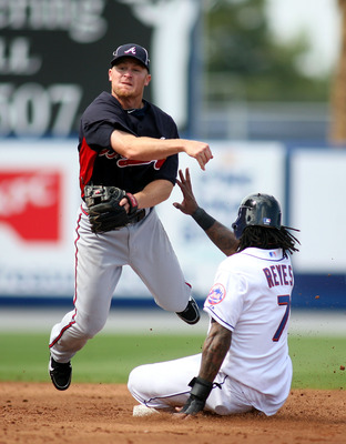 PORT ST. LUCIE, FL - FEBRUARY 26: Second baseman Brooks Conrad #7 of the Atlanta Braves turns a double play against Jose Reyes #7 of the New York Mets at Digital Domain Park on February 26, 2011 in Port St. Lucie, Florida.  (Photo by Marc Serota/Getty Ima