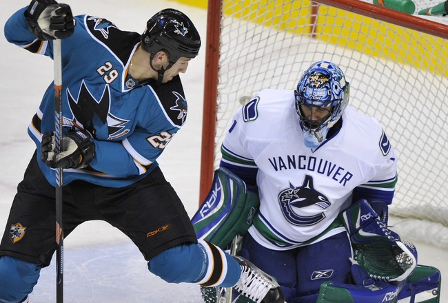 VANCOUVER, CANADA - OCTOBER 15:  Ryane Clowe #29 of the San Jose Sharks tries to back hand a shoot past goaltender Roberto Luongo #24 of the Vancouver Canucks during their game at General Motors Place October 15, 2007 in Vancouver, Canada.  (Photo by Nick