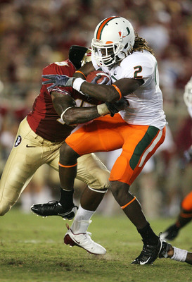 TALLAHASSEE, FL - SEPTEMBER 07:  Running back Graig Cooper #2 of the Miami Hurricanes is brought down by linebacker Mister Alexander #16 of the Florida State Seminoles at Doak Campbell Stadium on September 7, 2009 in Tallahassee, Florida.  (Photo by Doug