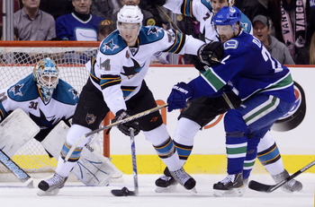 VANCOUVER, CANADA - JANUARY 20: Marc-Edouard Vlasic #44 of the San Jose Sharks holds off Daniel Sedin #22 of the Vancouver Canucks while trying to clear the puck during the third period in NHL action on January 20, 2011 at Rogers Arena in Vancouver, BC, C