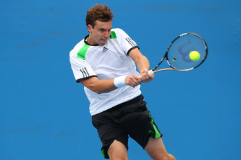MELBOURNE, AUSTRALIA - JANUARY 18:  Ernests Gulbis of Latvia plays a backhand in his first round match against Benjamin Becker of Germany  during day two of the 2011 Australian Open at Melbourne Park on January 18, 2011 in Melbourne, Australia.  (Photo by