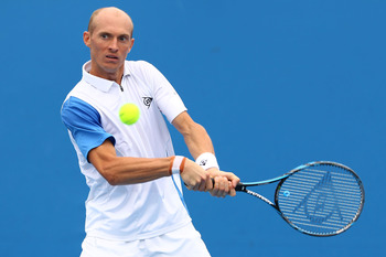 MELBOURNE, AUSTRALIA - JANUARY 17:  Nikolay Davydenko of Russia plays a backhand in his first round match against Florian Mayer of Germany during day one of the 2011 Australian Open at Melbourne Park on January 17, 2011 in Melbourne, Australia.  (Photo by