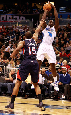 ORLANDO, FL - DECEMBER 06:  Brandon Bass #30 of the Orlando Magic attempts a shot over Al Hoford #15 of the Atlanta Hawks during the game at Amway Arena on December 6, 2010 in Orlando, Florida. NOTE TO USER: User expressly acknowledges and agrees that, by