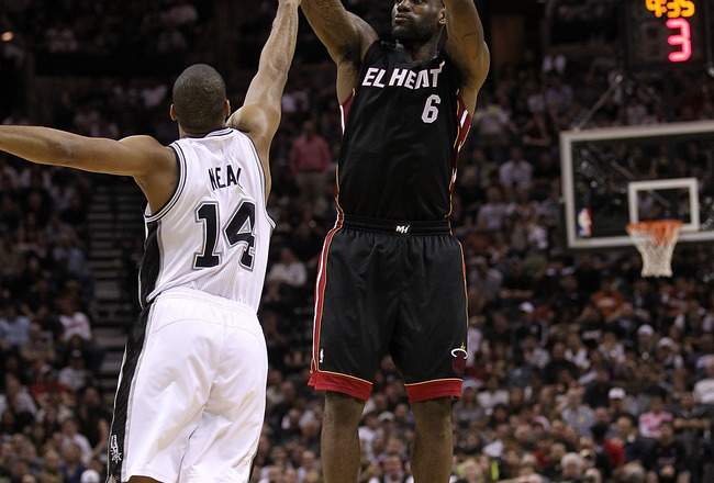 SAN ANTONIO, TX - MARCH 04:  Forward LeBron James #6 of the Miami Heat takes a shot against Gary Neal #14 of the San Antonio Spurs at AT&T Center on March 4, 2011 in San Antonio, Texas.   NOTE TO USER: User expressly acknowledges and agrees that, by downl