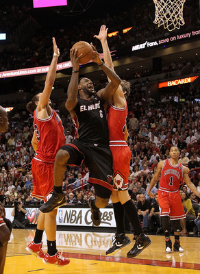 MIAMI, FL - MARCH 06:  LeBron James #6 of the Miami Heat shoots over Joakim Noah #13 and Omer Asik #3 of the Chicago Bulls during a game at American Airlines Arena on March 6, 2011 in Miami, Florida. NOTE TO USER: User expressly acknowledges and agrees th